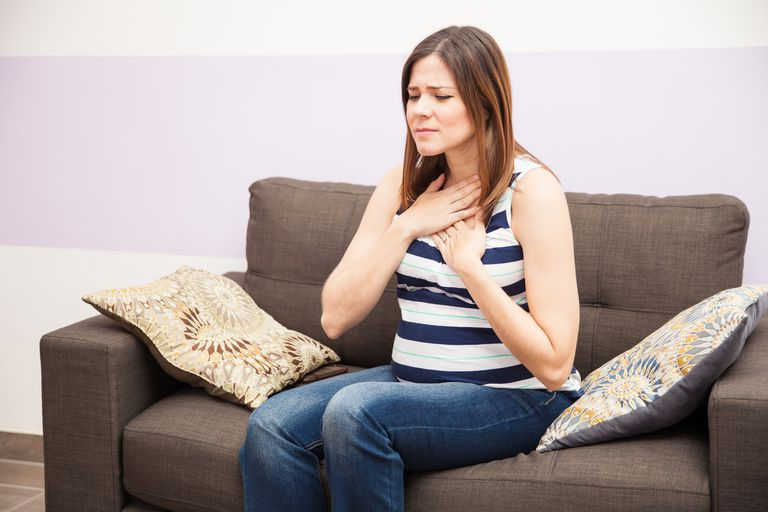 woman holding her hands on chest due to heartburn