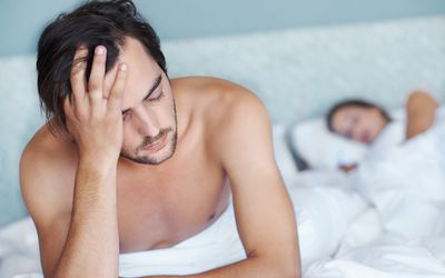Man looking distraught in bed