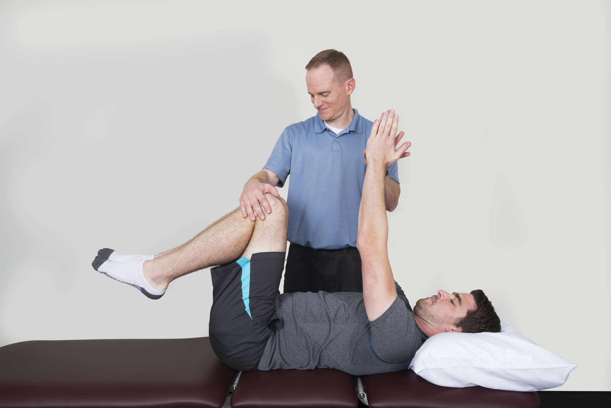physical therapist assisting man with core exercise