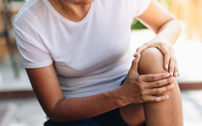 Midsection Of Woman With Knee Pain Sitting Indoors