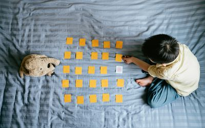 Young boy sitting on bed, lining up pieces of paper