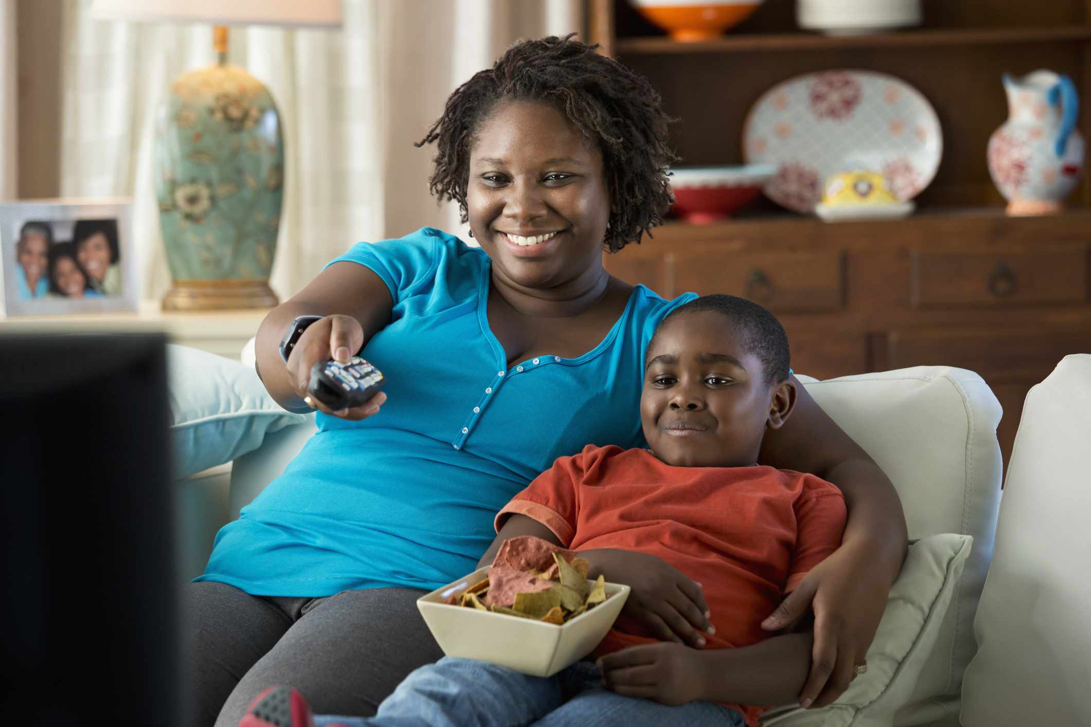 Black mother and son watching television together