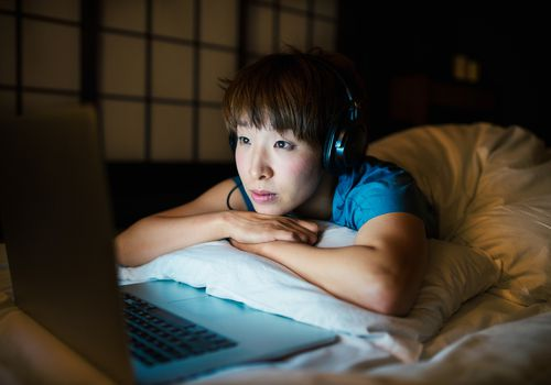 Woman in bed looking at laptop in the dark