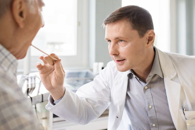 Otolaryngologist examines sore throat of senior patient