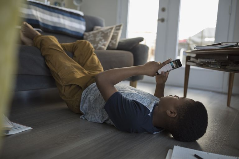 Teenage boy laying, using cell phone on living room sofa