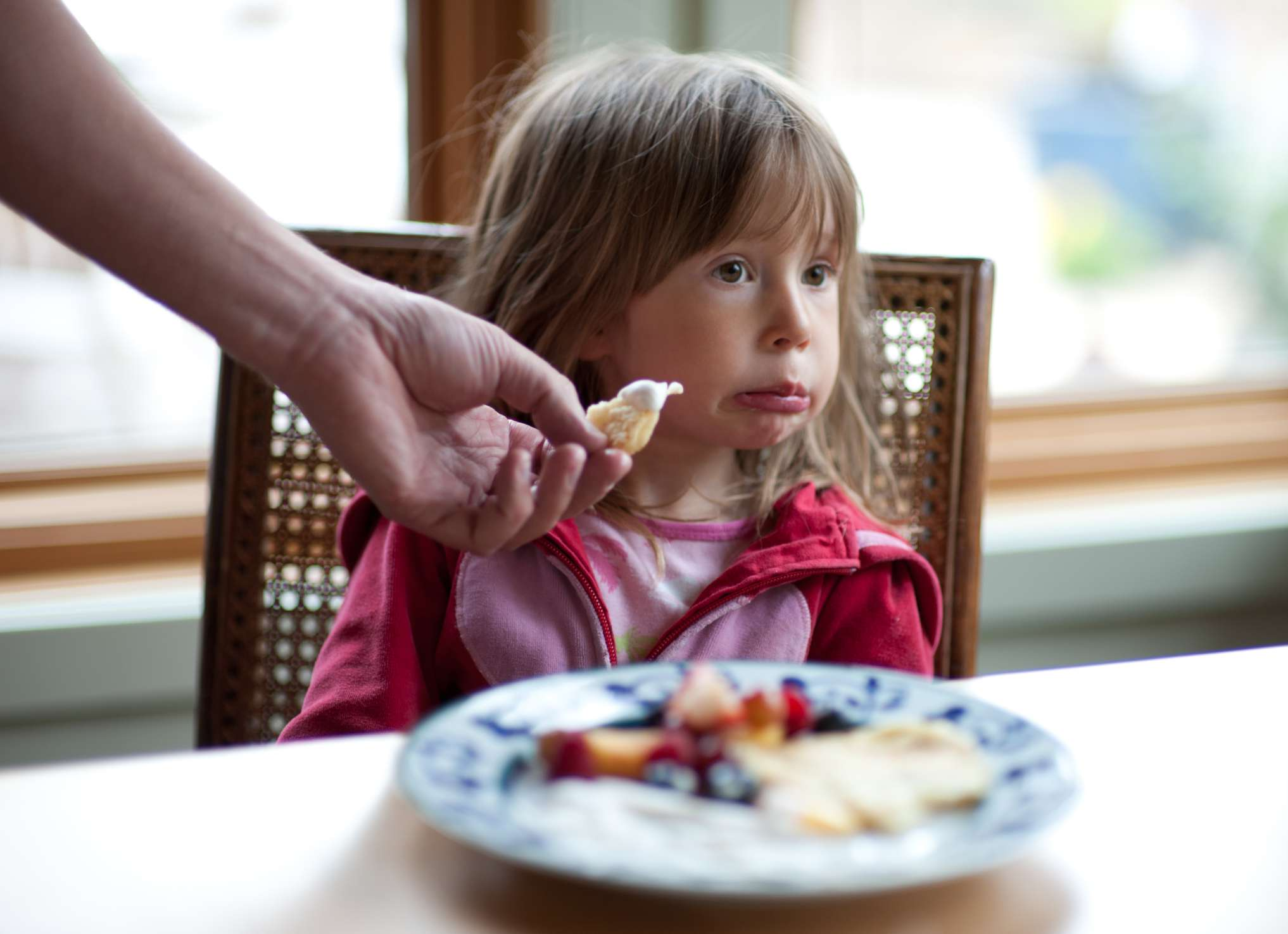 Young child refusing to eat their food at dinner table