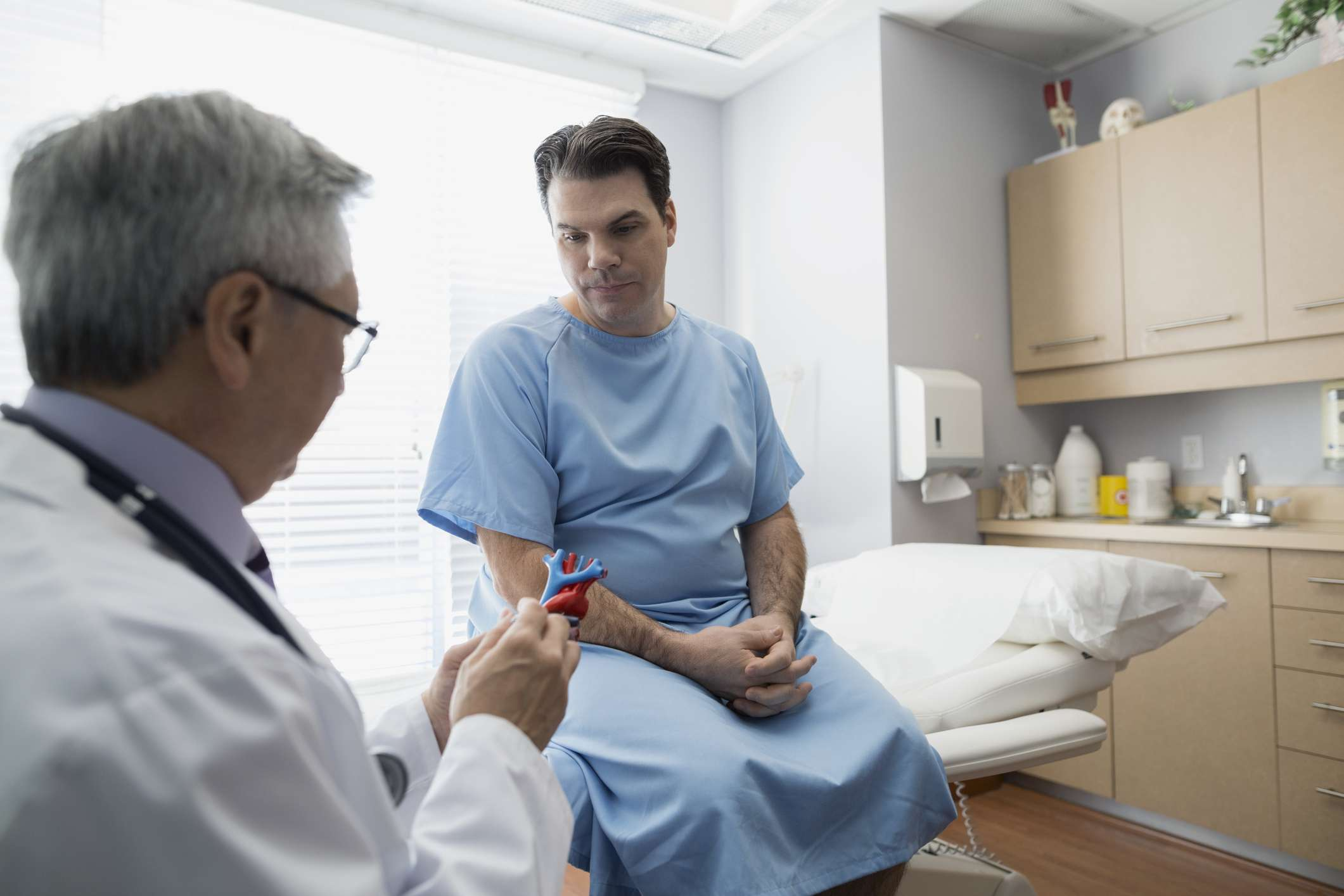 A doctor explaining a model to patient in examination room