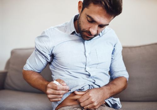 Young white man with dark hair and facial hair giving himself an injection in his abdomen.