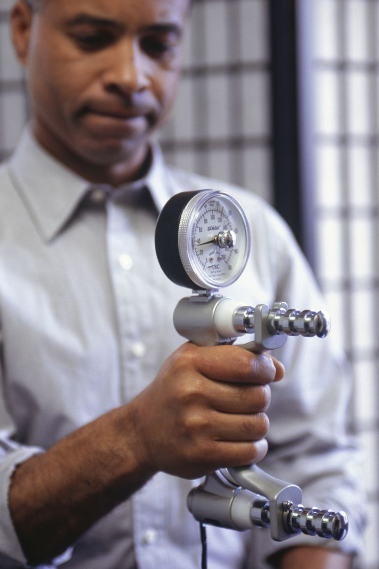 man testing grip strength with dynamometer
