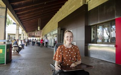 Woman with muscular dystrophy uses a powered wheelchair to go to lunch at cafeteria
