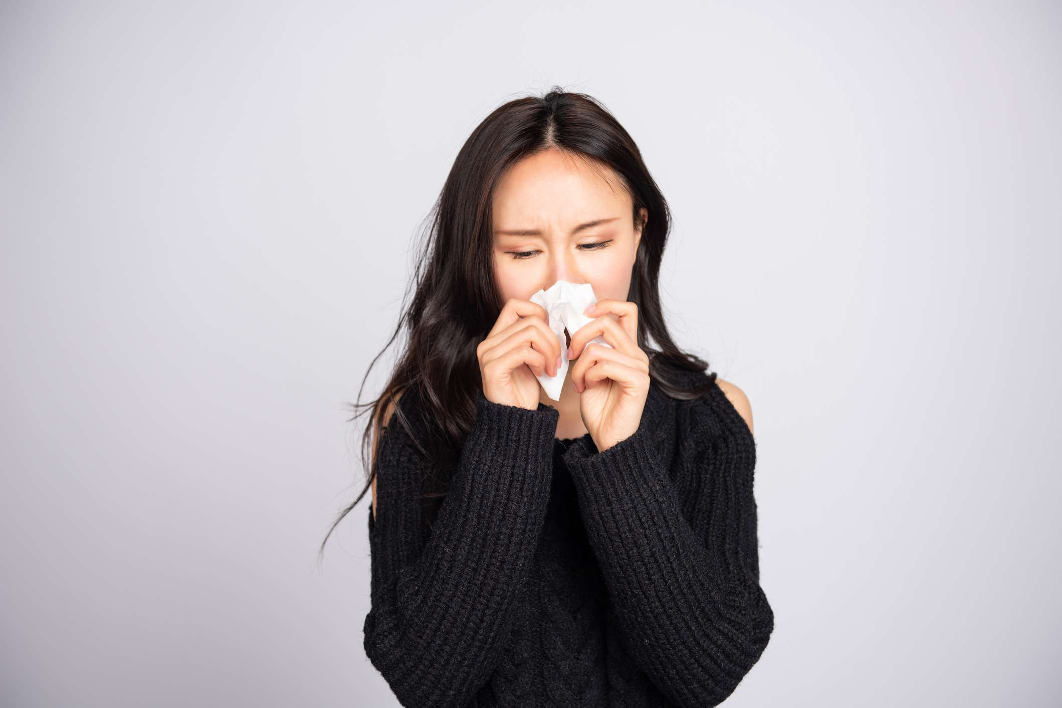 A young Asian woman in a black sweater is blowing her nose.