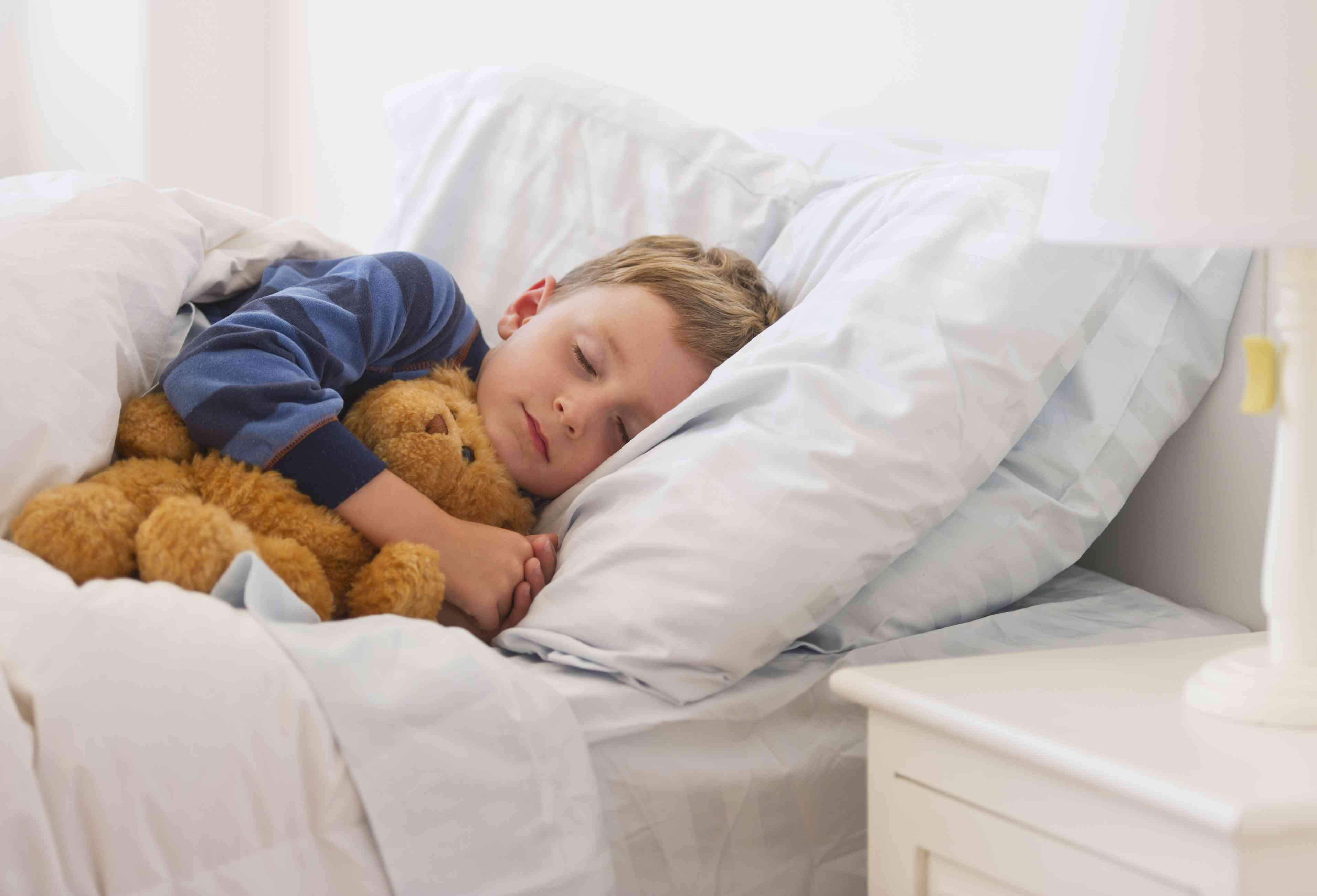 A boy sleeping in his bed with his teddy bear