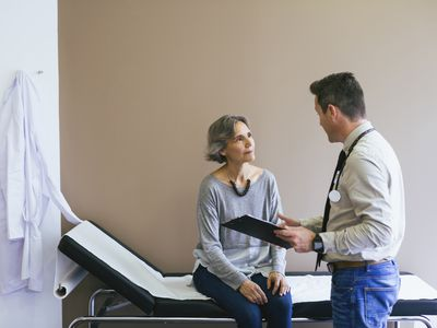 Senior patient talking with doctor while sitting on bed against wall at hospital