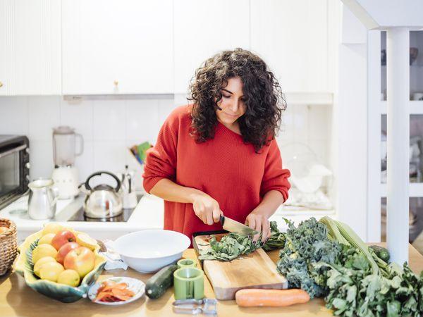 Brunette woman making a healthy green salad