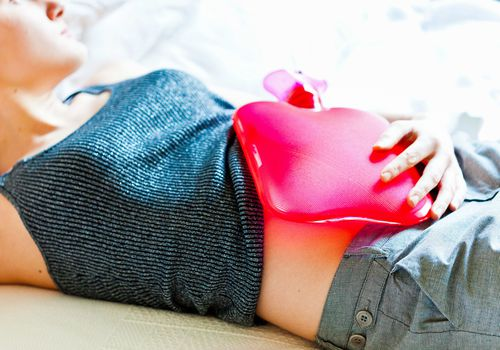 Woman using a hot-water bottle on her belly to relieve abdominal pain.