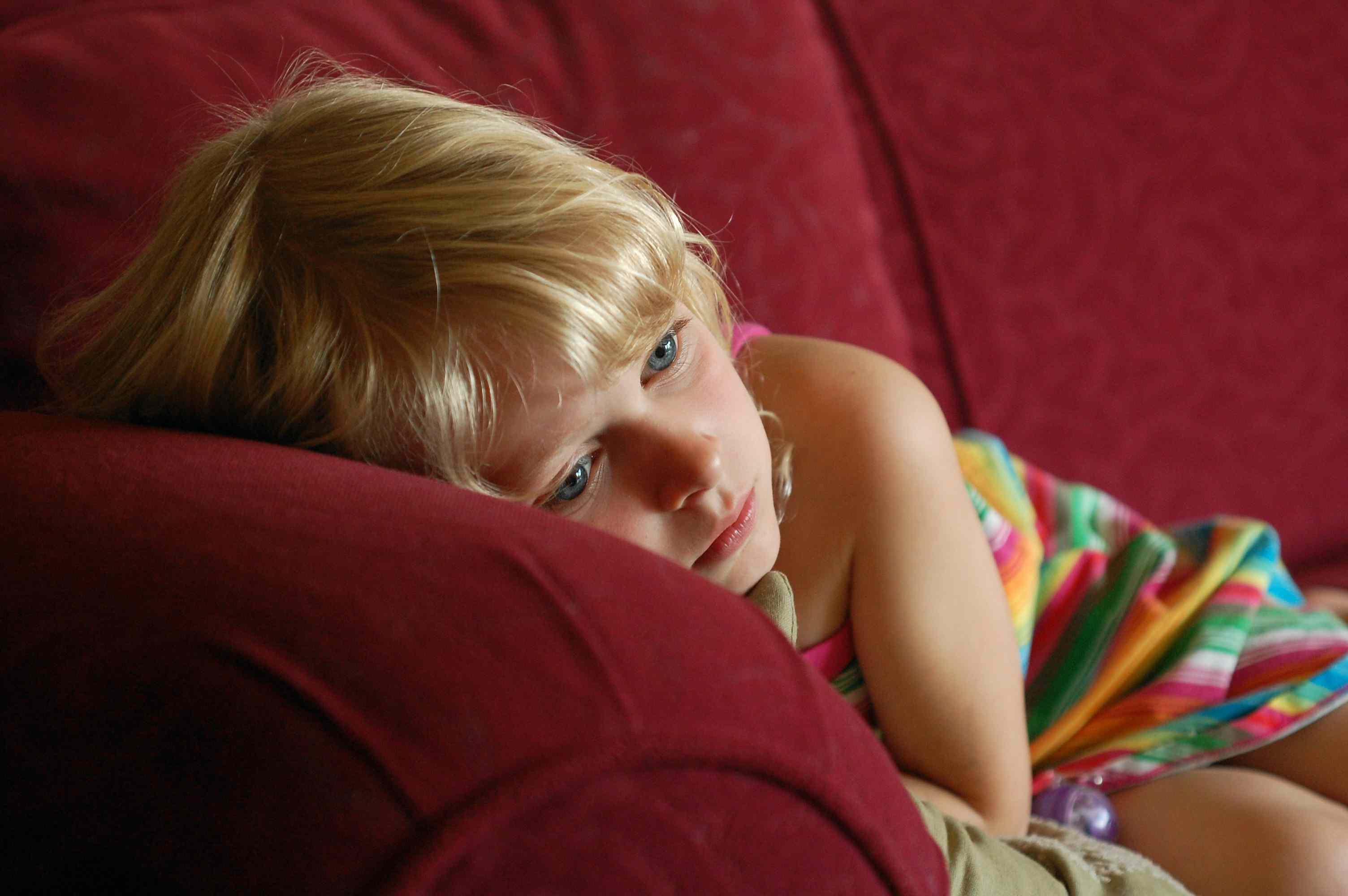 Sad young girl laying on a sofa