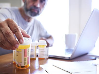 A man reading the labels on his prescription