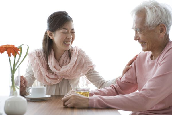 asian woman laughing at a table with an older asian man