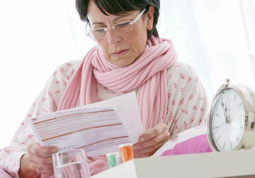woman looking at health insurance paperwork