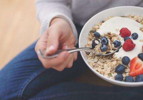 Woman eating health breakfast yogurt bowl.