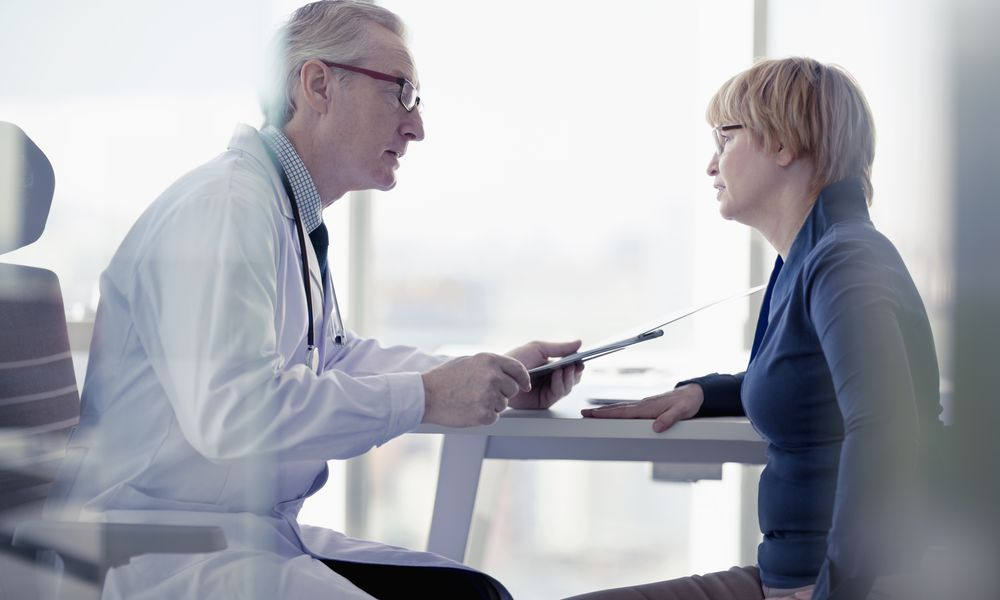 Doctor talking to patient at desk in office
