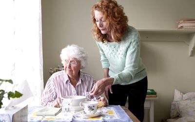 Woman feeding elderly woman