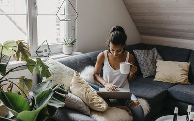 Young woman sitting on the couch with cup of coffee using laptop