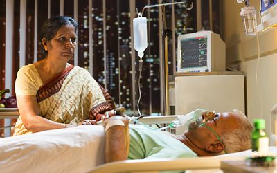 Male patient sleeping with his wife sitting by his side