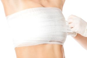Gauze being wrapped around a woman's breasts after surgery
