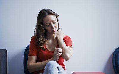 woman scratching rash on arm