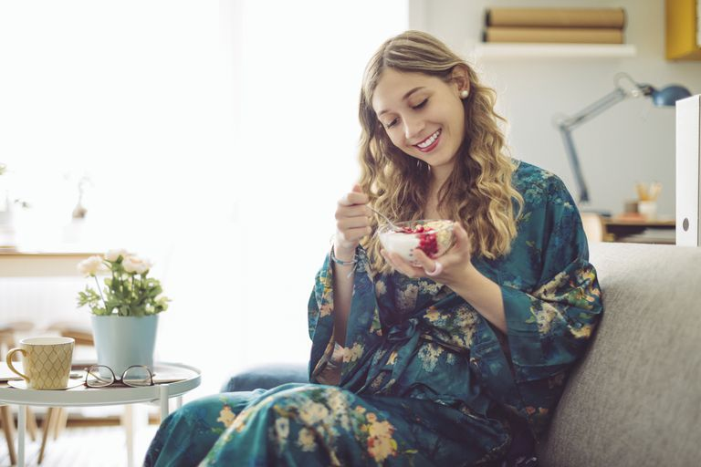 Woman eating yogurt on couch