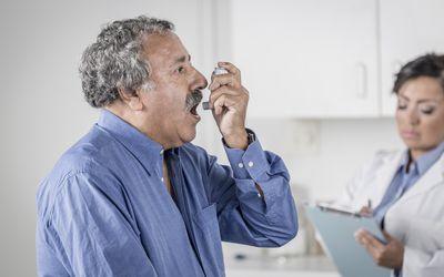 Senior man using asthma inhaler in doctor's office