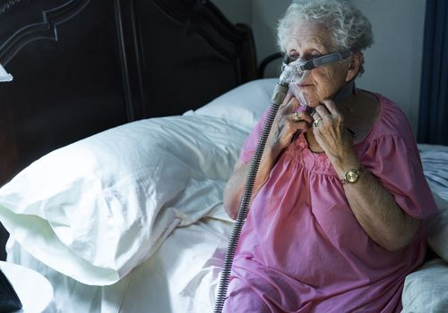 Older woman putting on her CPAP machine at night.