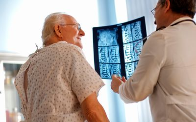 Senior man discussing X-ray with doctor.