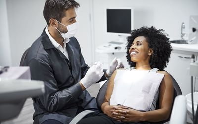 Dentist examining smiling female patient in clinic - stock photo