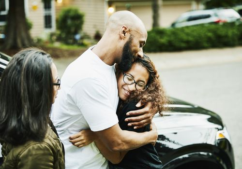 Smiling father and daughter embracing after driving lesson