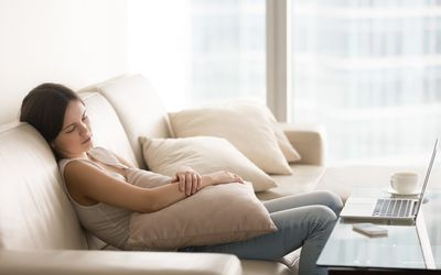 Young pretty woman sleeping on couch, taking nap on sofa