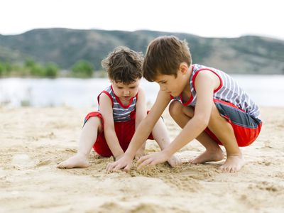Siblings playing in the sand