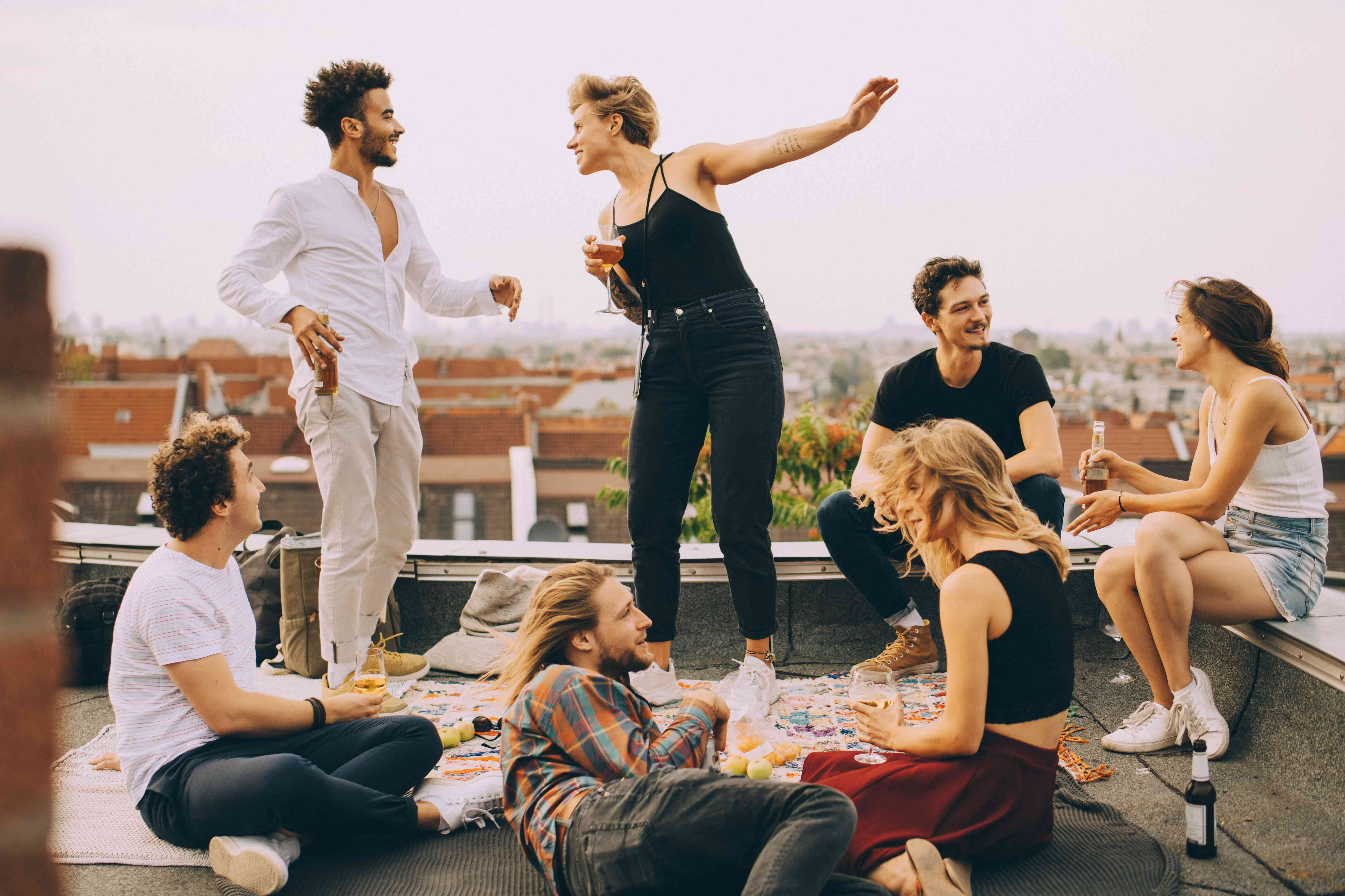 Happy people dancing while enjoying music with friends on terrace at rooftop party