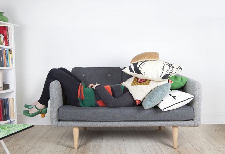 woman covered with pillows on couch