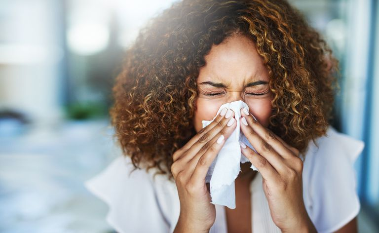 A woman blowing her nose because of allergies