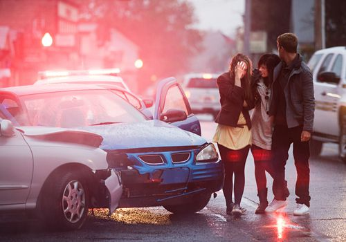 a young woman comforting another woman who's been in a car crash