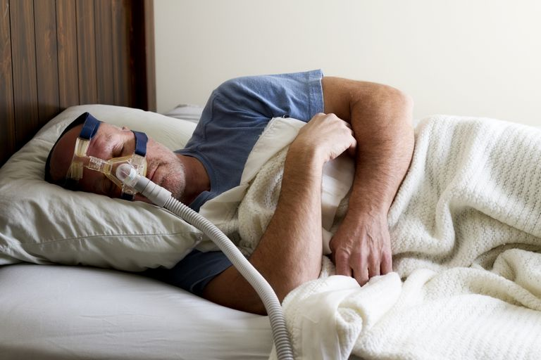 man wearing CPAP machine in bed
