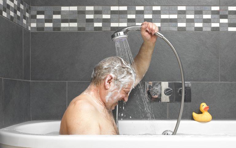older man taking a shower in a bathtub