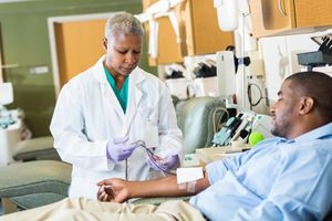 Phlebotomist checking line while patient donates blood in hospital