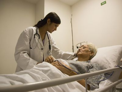 A doctor talking to her elderly patient who is laying in a hospital bed.