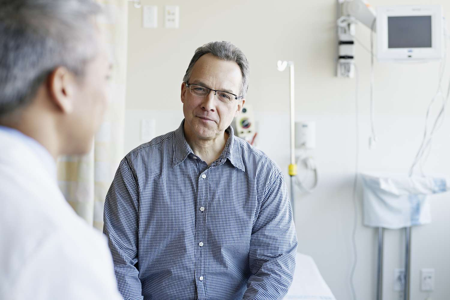 A doctor talking to his patient in a hospital room