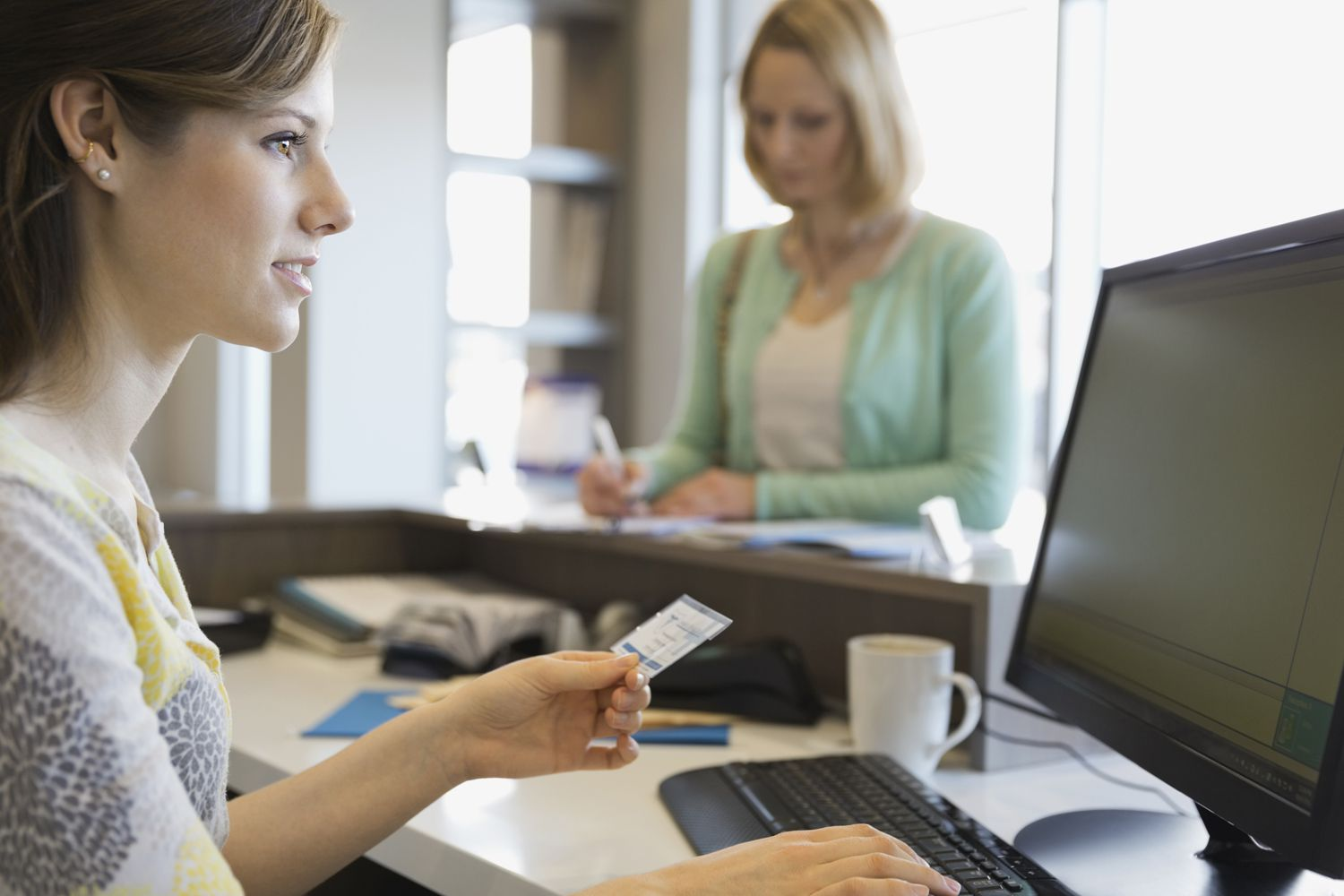 A receptionist examines a patient's insurance information