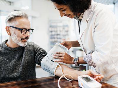 Pharmacist Measuring Mature Man's Blood Pressure