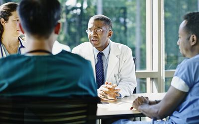Physicians at a table discussing a case.
